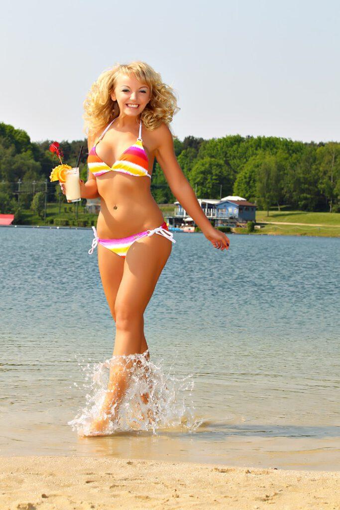 Model im Bikini posiert am See im Wasser