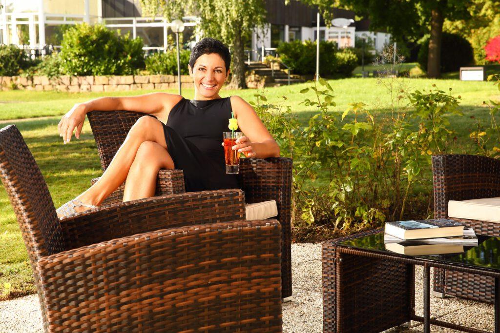 Frau präsentiert Gartenstühle aus Rattan