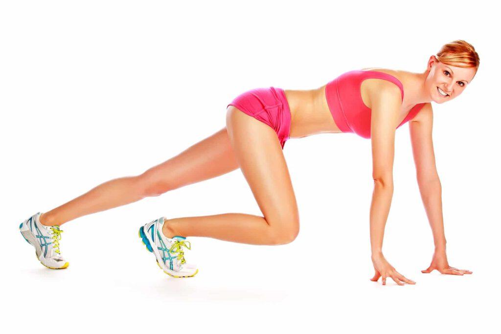 Modell in knapper Sportkleidung in Sprinterpose und langen Beinen