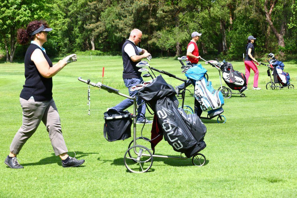 Golfspieler mit Trolleys beim Golfturnier