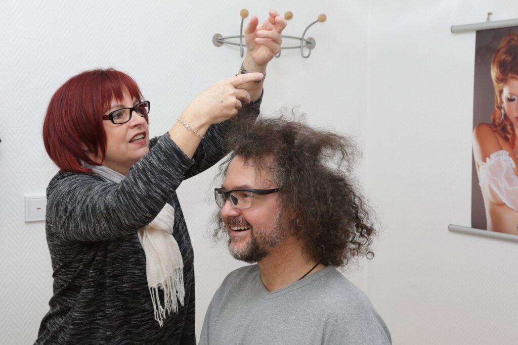 Friseurin frisiert Personen für Fotoaufnahmen