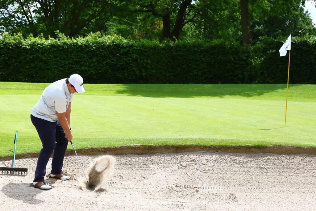 Spieler schlägt Golfball aus Bunker