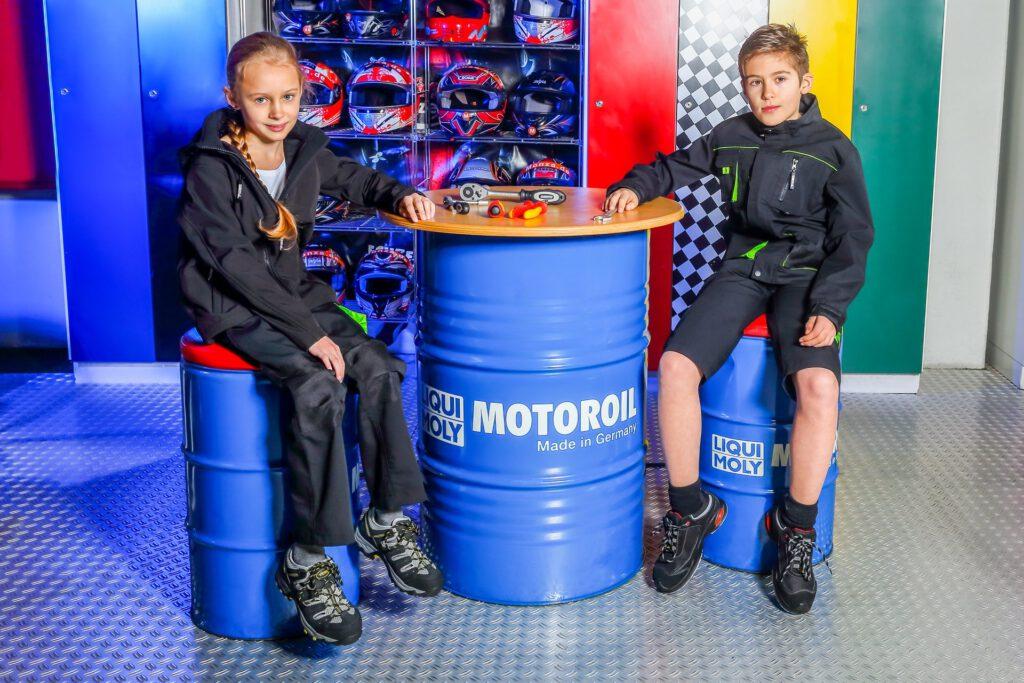 Zwei Kinder zeigen coole Arbeitskleidung an der Rennbahn